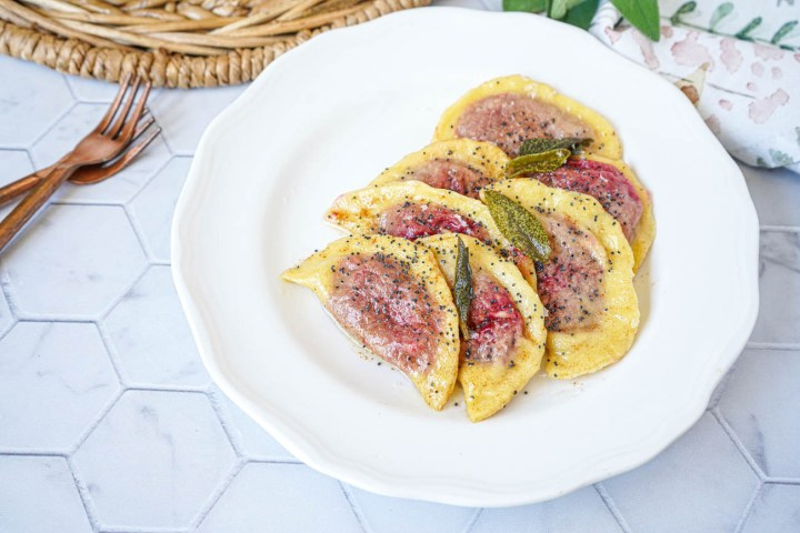 Casunziei All'Ampezzana (Beet Filled Pasta with Poppy Seeds) on a white plate with sage leaves.