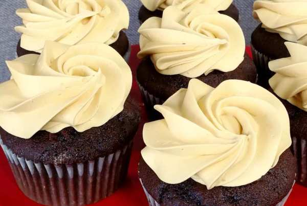 chocolate cupcakes with caramel icing on a red platter