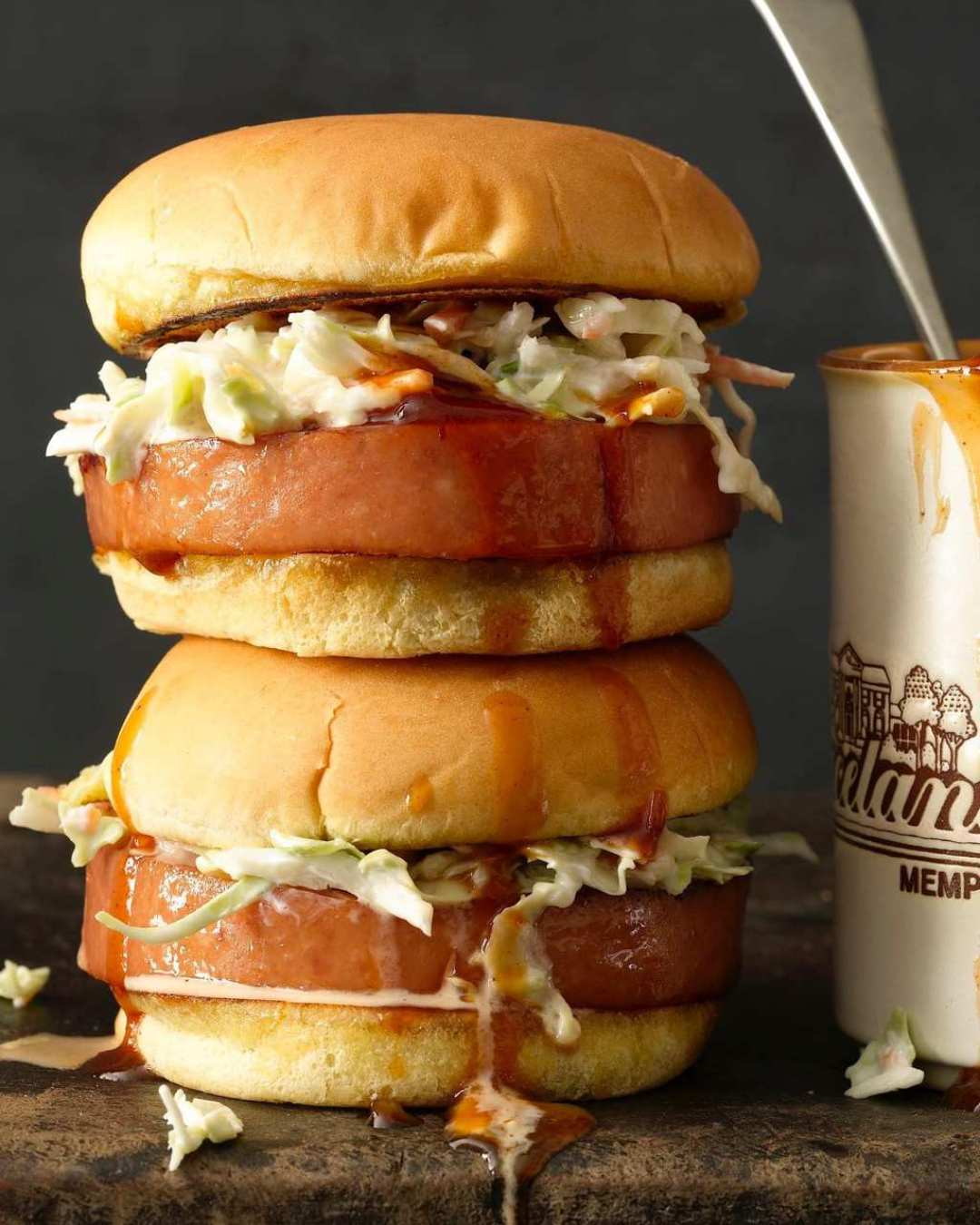 Stacked Memphis Smoked Bologna Sandwiches with coleslaw on hamburger buns