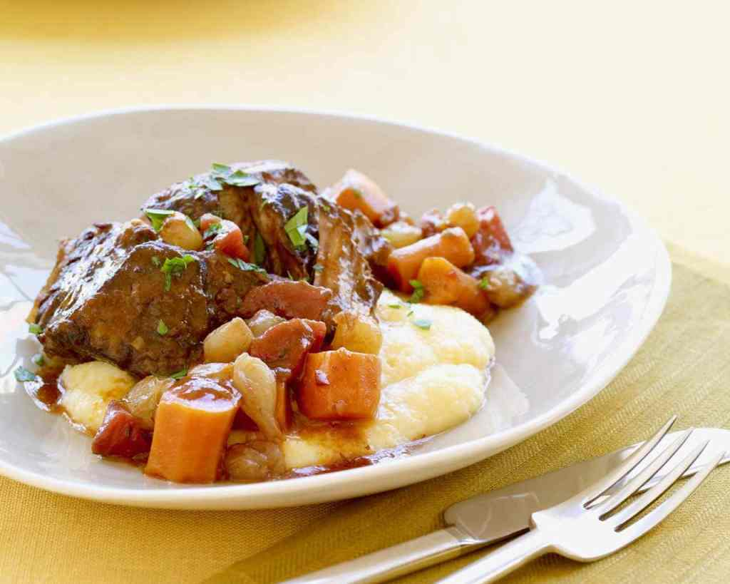 Braised short ribs with vegetables and polenta in a white bowl