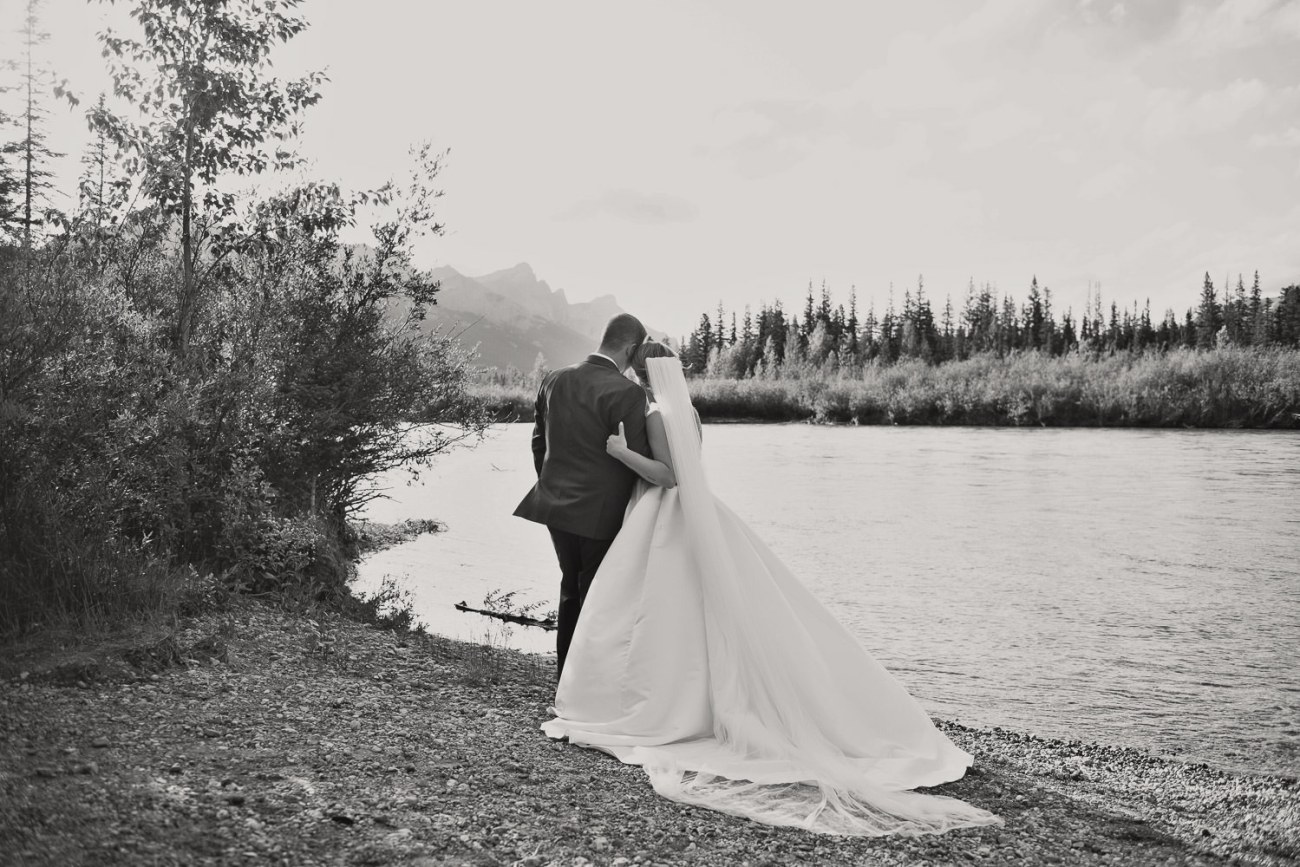 Bride and groom pose on the Bow River in Canmore captured by Tara Whittaker Photography