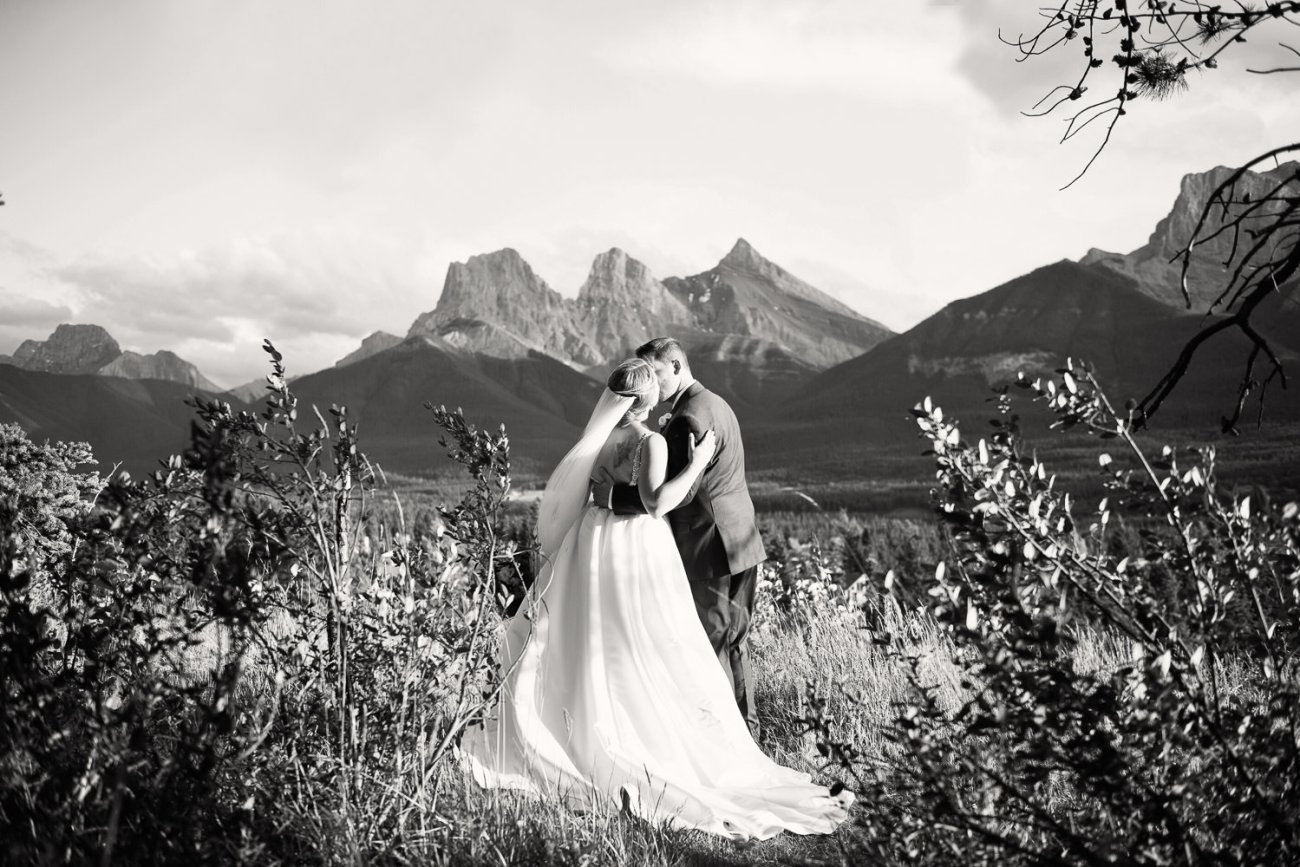 Black and white portrait of bride and groom with the Three Sisters in Canmore captured by Tara Whittaker Photography