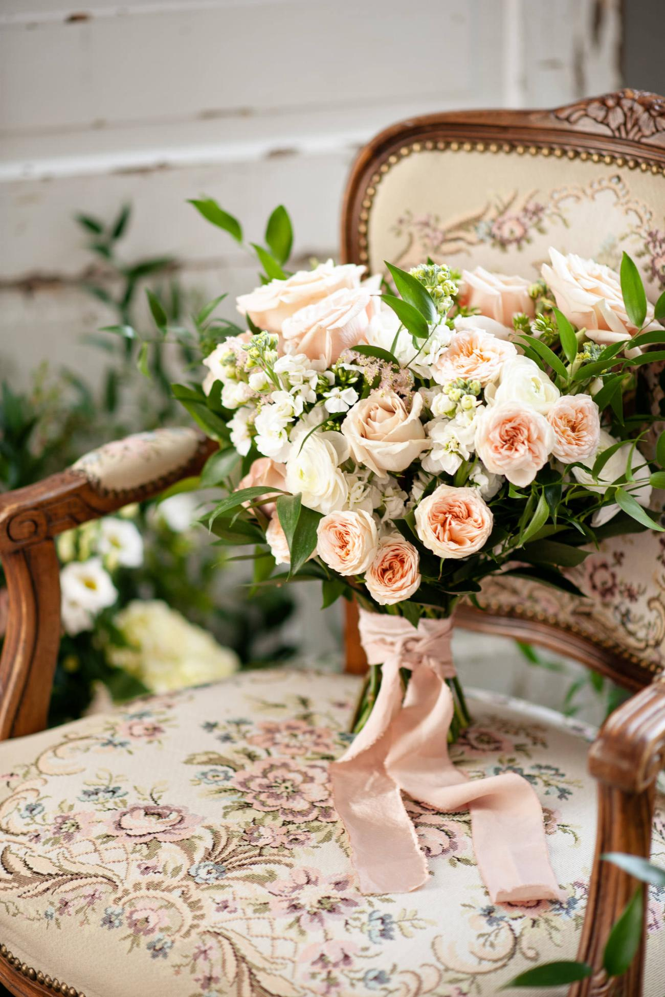 bridal bouquet sits on a vintage chair captured by Tara Whittaker Photography