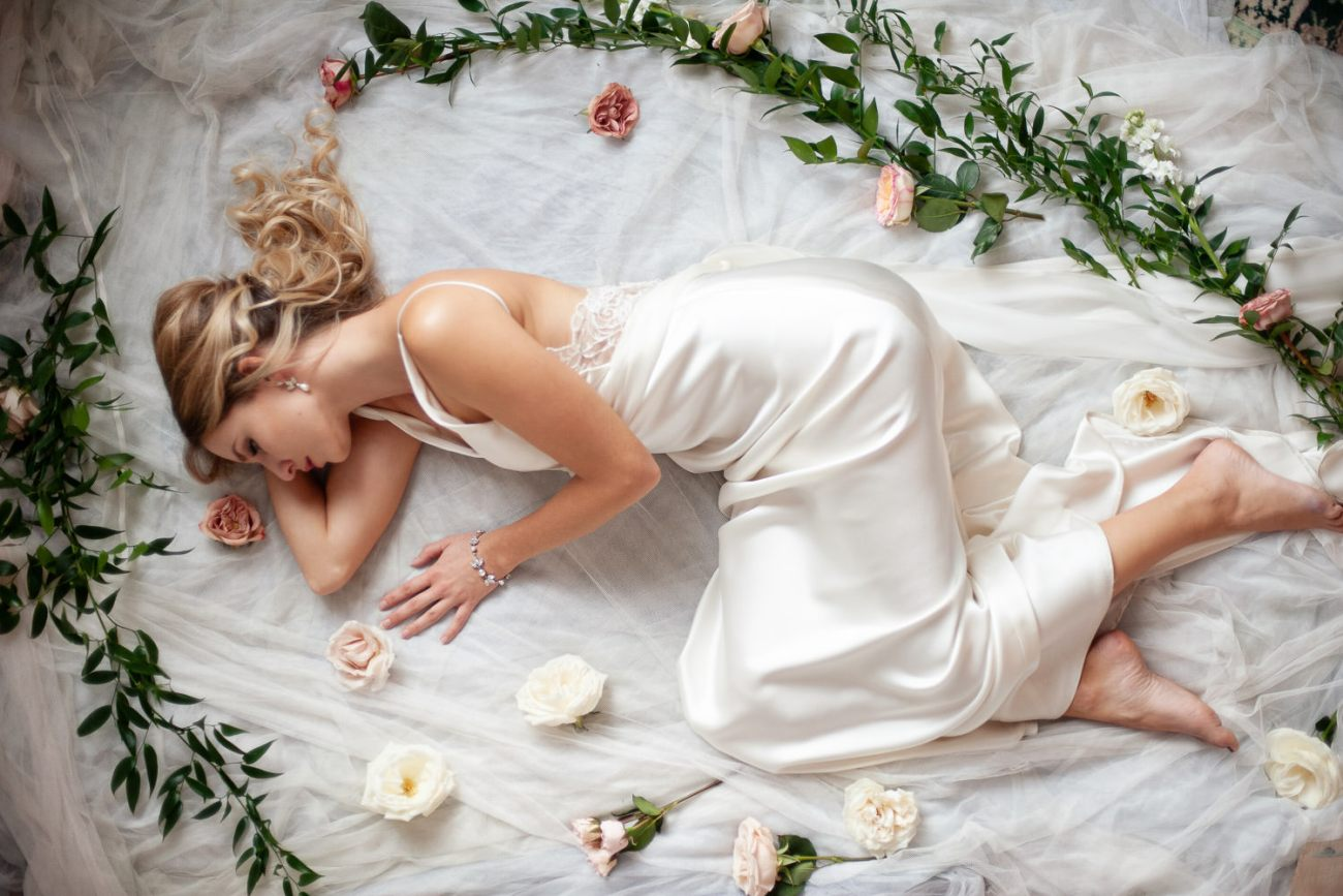 bride lying amongst flowers and greenery captured by Tara Whittaker Photography
