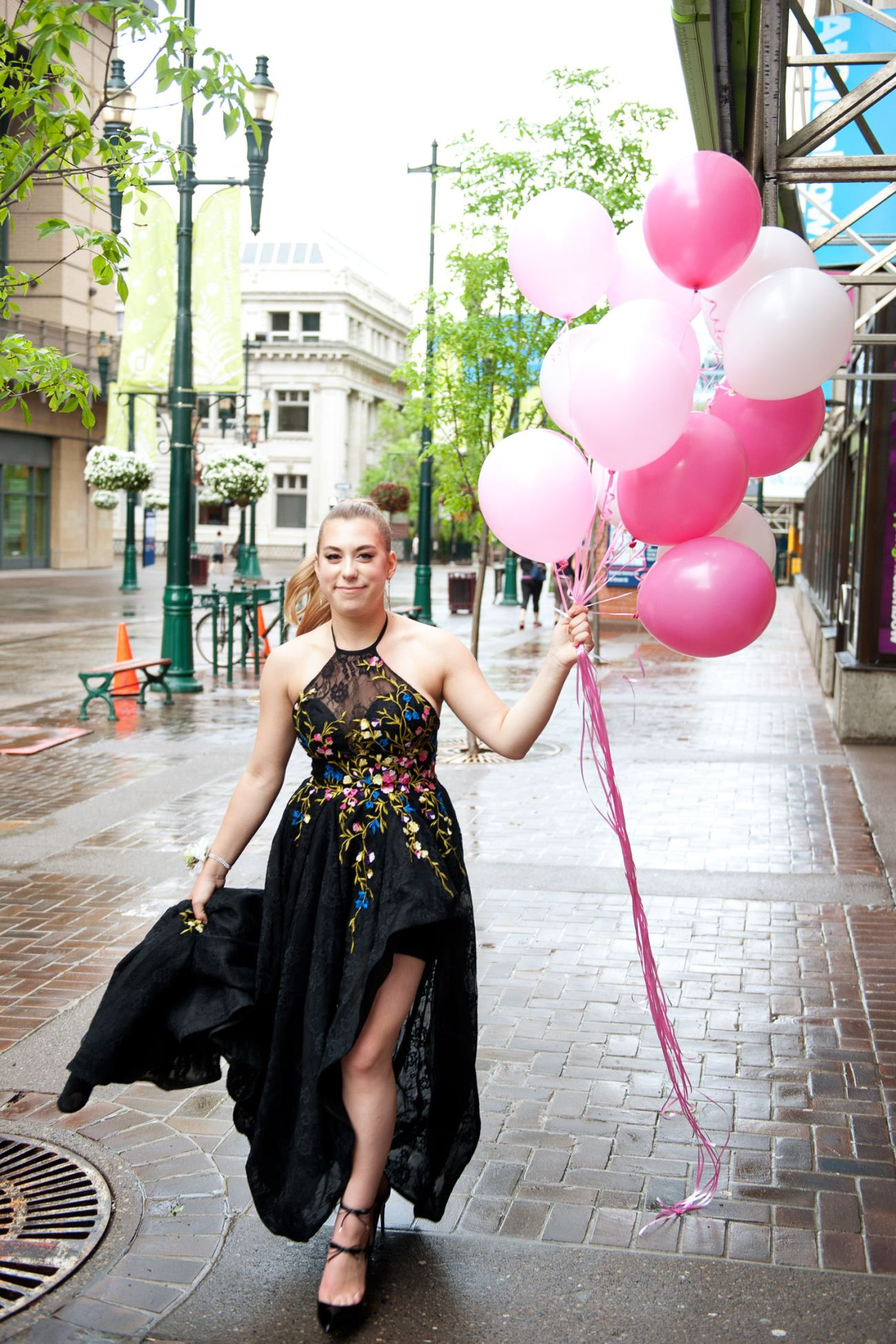 graduate carrying pink balloons on the way to her grad captured by Tara Whittaker Photography