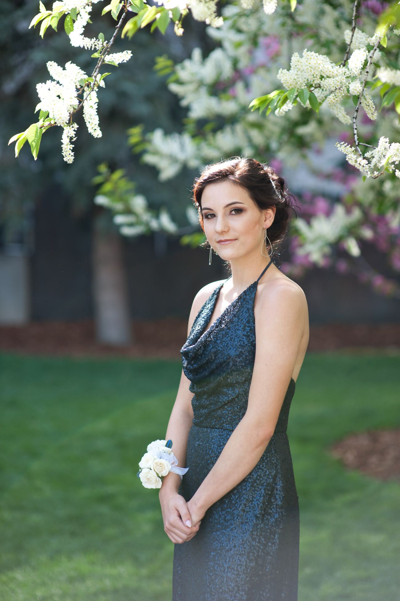 graduate poses with a blossoming tree captured by Tara Whittaker Photography
