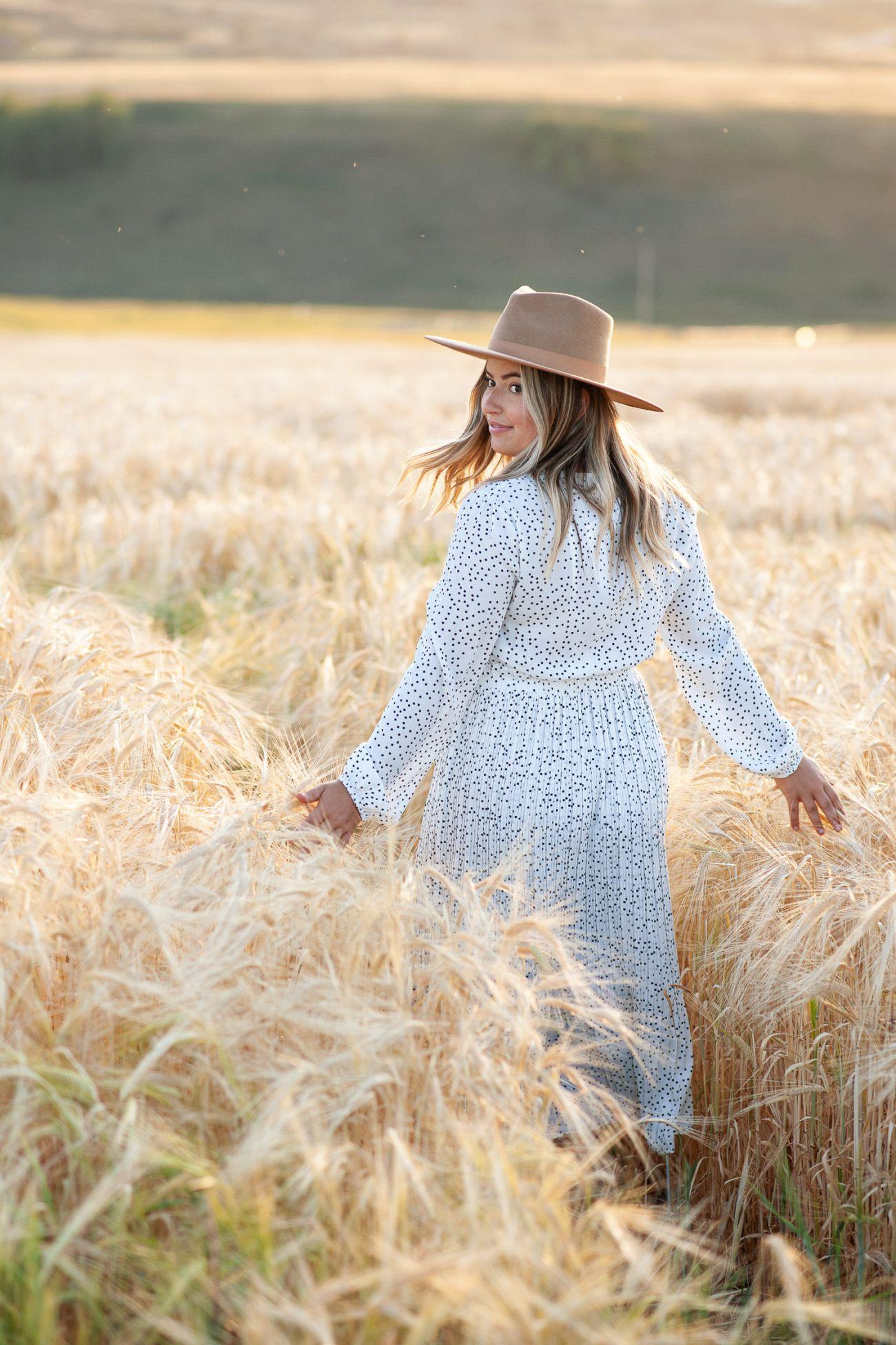 bride walks through a field of barley captured by Tara Whittaker Photography