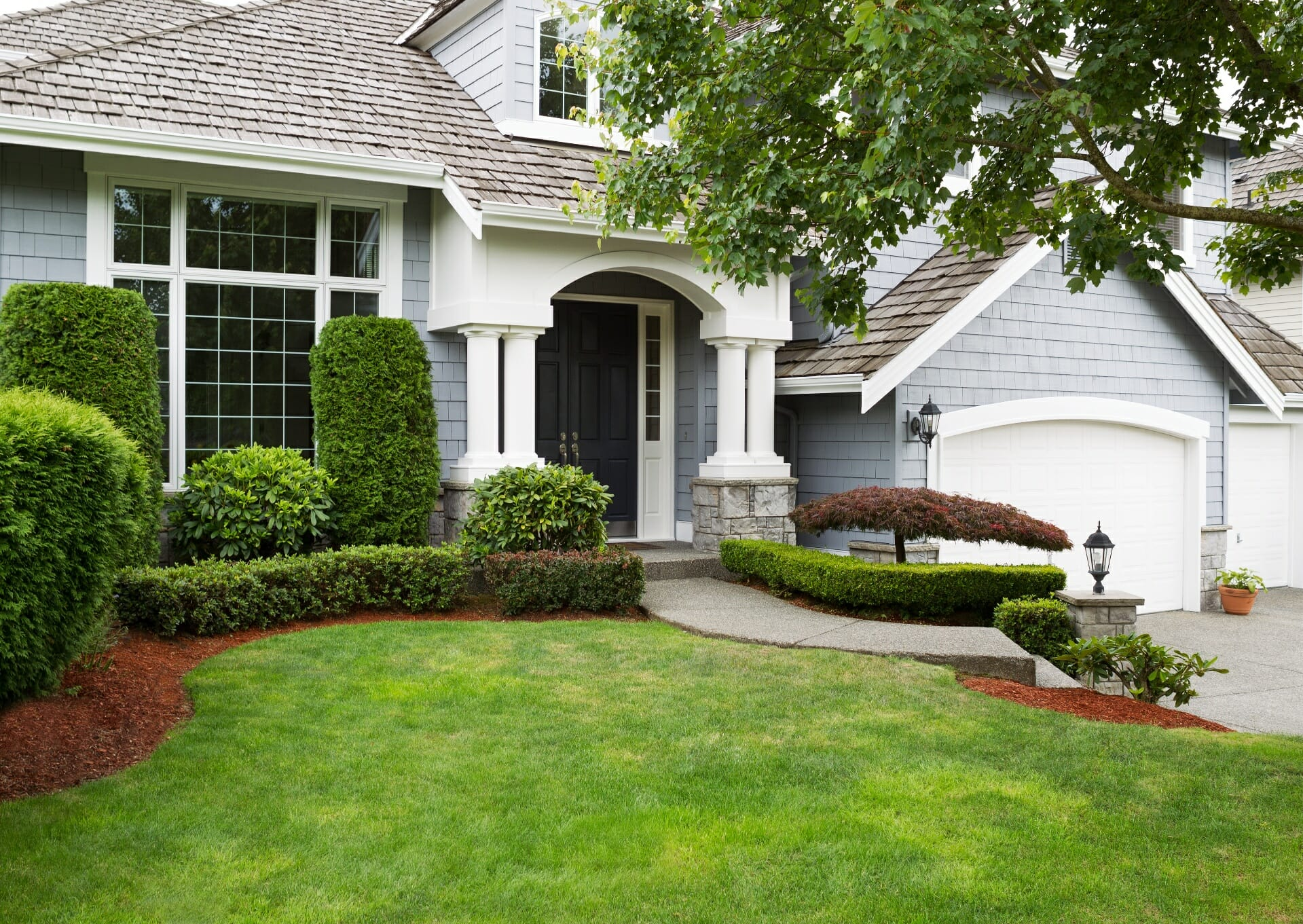 A blue shingled Cape Cod-style home with white columns and a neatly manicured front lawn.