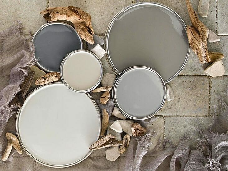 Paint can tops lay on top of tiling. Paints ranging from taupe to dark gray.