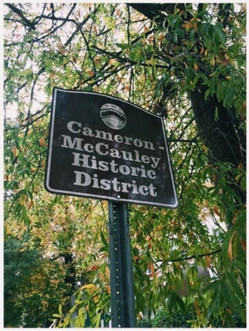 The Cameron-McCauley Historic District sign in the afternoon. Green and brown leaves and a tree in the background.