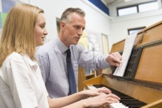 3204179-female-student-learning-piano-with-teacher-in-classroom