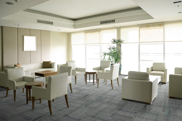 """""""Bright airy waiting room filled with modern white furniture. Picture on wall is white, ready for copy to be added."""""""
