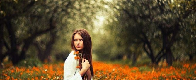 Benefits of Tarot Card Reading young woman seated in a field of orange flowers surrounded by walls of trees and looking concerned