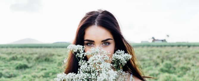 Developing Psychic Abilities brunette woman in field holding a bouquet of white wildflowers