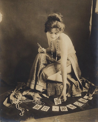 Old phote of a gypsy woman she has no top on but you really cant see anything she is neeling and giving a tort card reading