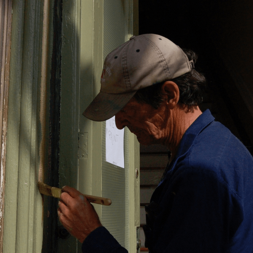 Volunteer Joe DeLuccy painting the entrance doors in 2008. When he isn't painting, he is polishing the brass.