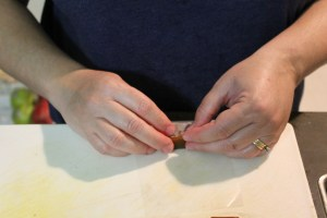 "Start by placing a pice of the caramel on a piece of the paper about 1"" from the end closest to you."