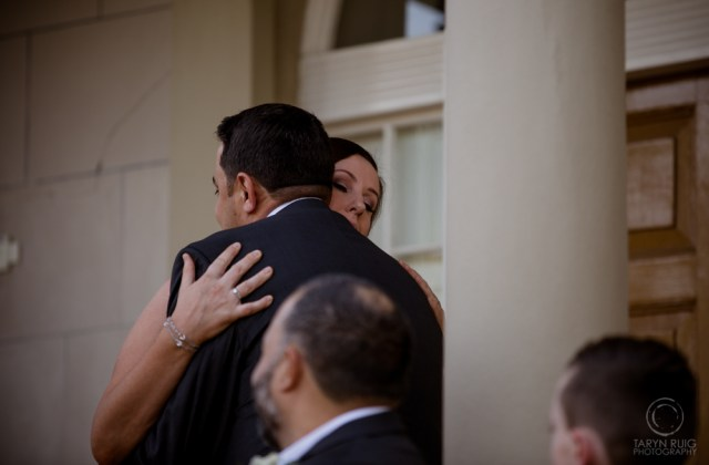 bride and groom hugging at old government house