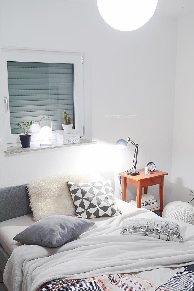 Schlafzimmer gemütlich modern skandinavisch schlicht am Abend einrichten: Tischleuchten, Wohntextilien in weiß + grau, Bildbände. Tasteboykott.