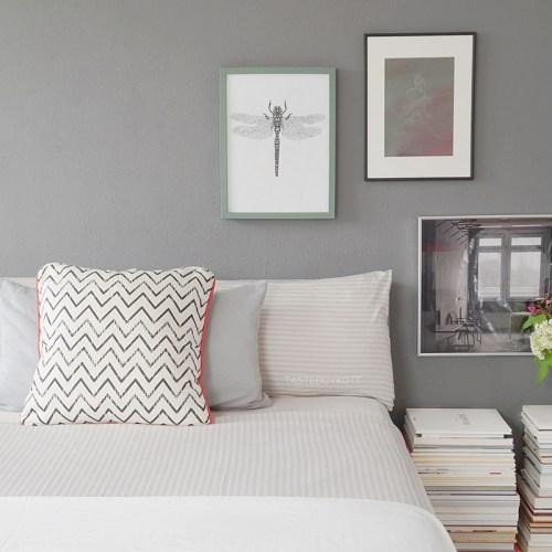 Skandinavisch monochromes Schlafzimmer mit dunkelgrauer Wandfarbe, Polsterbett, Kunst als Wanddeko, modernen weißen Kissen und Bücherstapeln als Nachttisch einrichten. Wohnideen Deko Wohninspiration Tasteboykott Wohnblog.