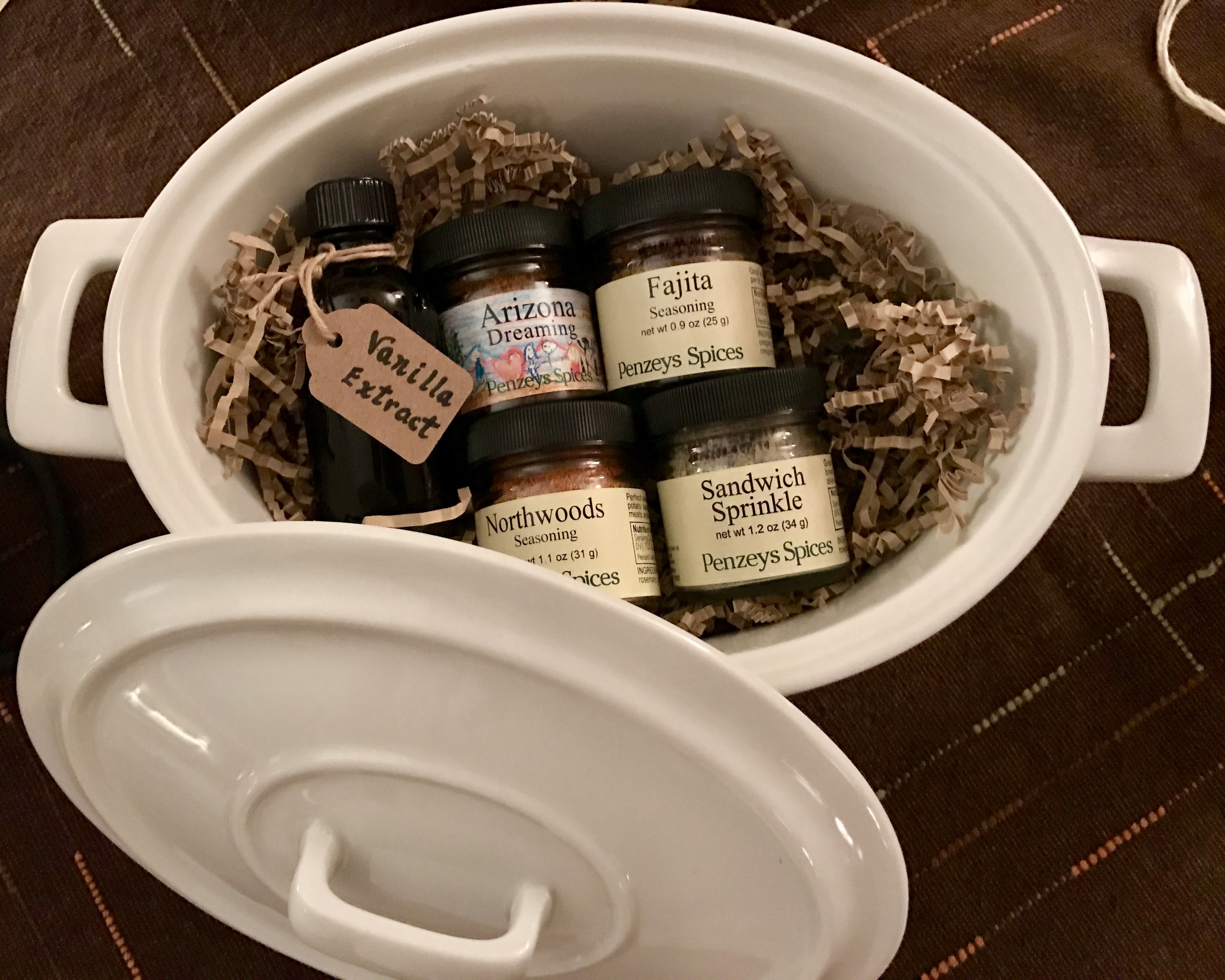 Bottled spices and homemade vanilla extract in a dish for creative gift given for a cook