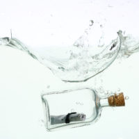 Glass bottle with message inside submerged in water to represent Client Testimonials, Testimonials, former clients, work