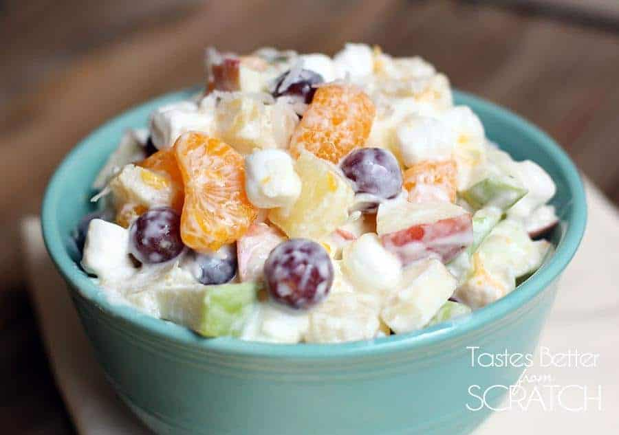 Creamy Fruit Salad Recipe from TastesBetterFromScratch.com - all of my favorite fruits mixed with mini marshamallows and coconut and coated in greek yogurt! A healthy side and delicious!