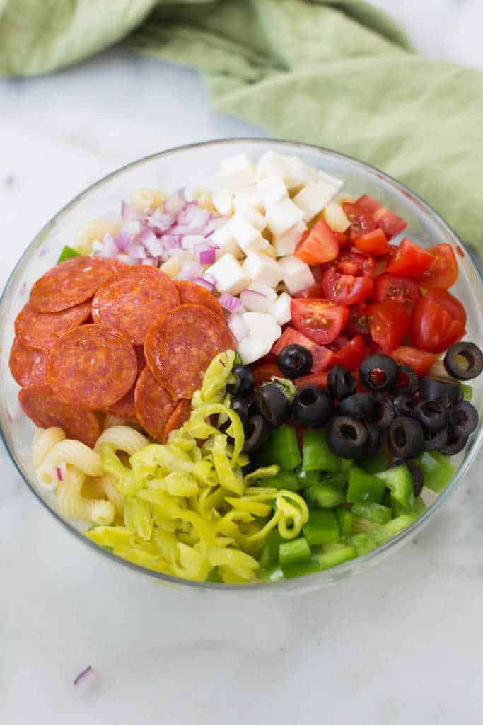 Ingredients for pizza pasta salad including pepperoni, olives, tomatoes, onion, mozzarella cheese, parmesan cheese, green bell peppers, pepperocini peppers. | tastesbetterfromscratch.com