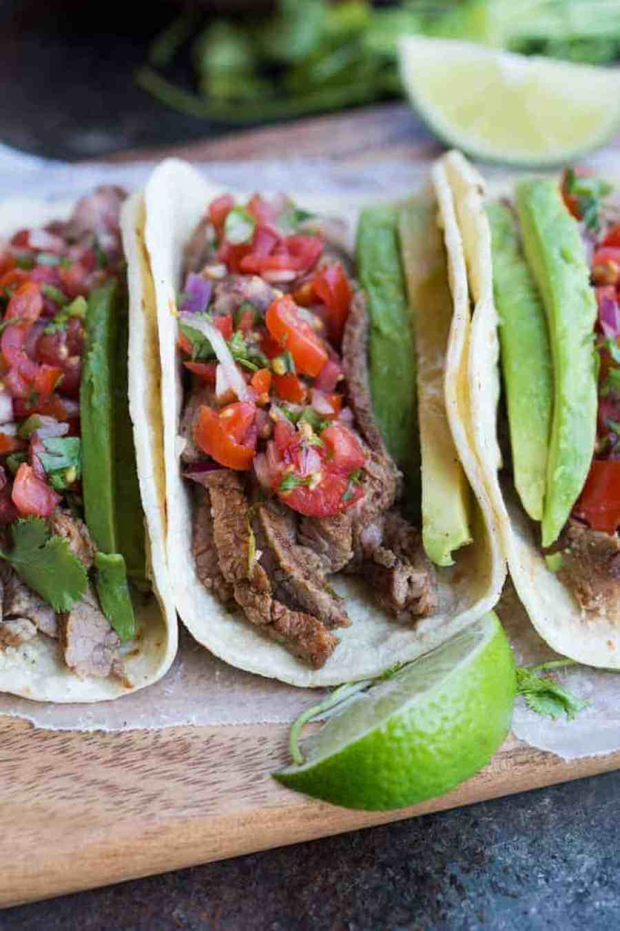 Carne Asada Tacos just as good as ones you could buy off the street in Mexico! Juicy, tender, marinated steak tacos served on a warm corn tortilla with fresh pico de gallo and avocado.   tastesbetterfromscratch.com