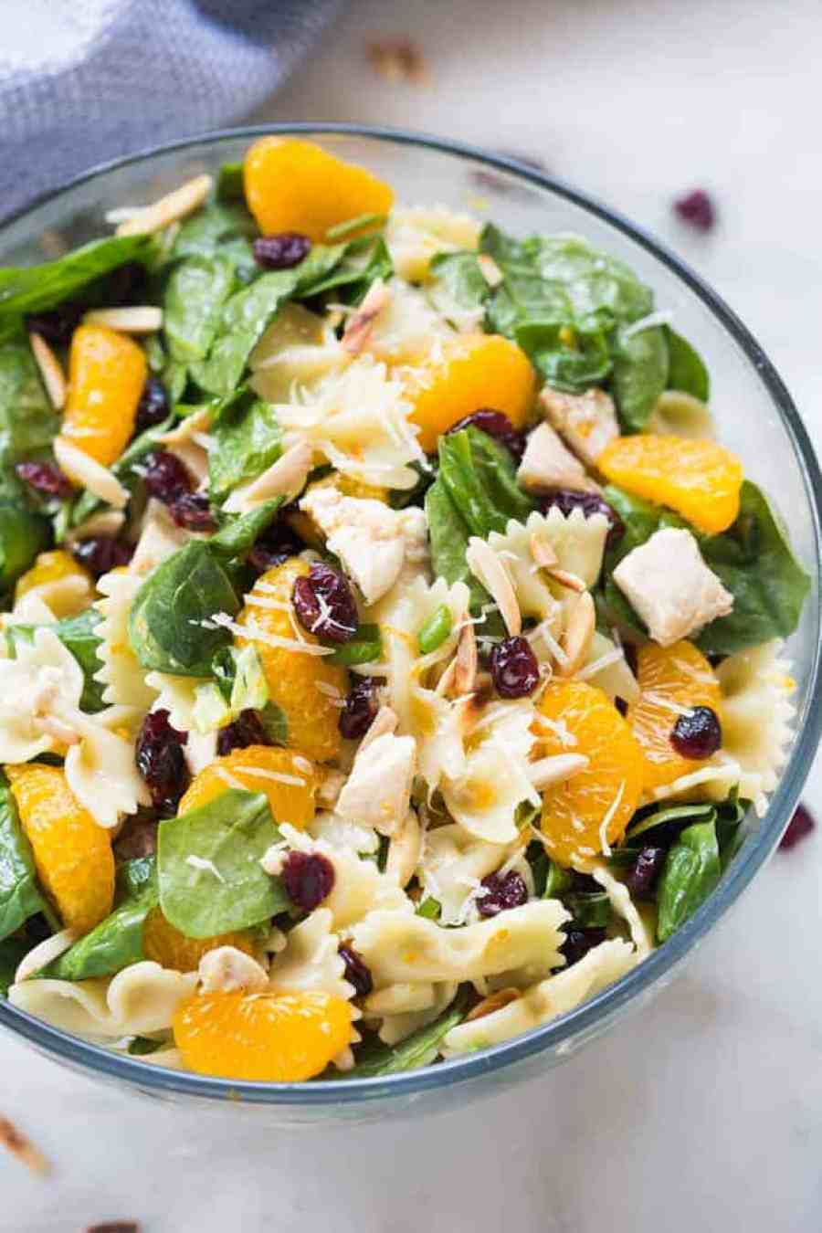 Healthy Chicken Pasta Salad loaded with spinach, mandarin oranges, craisins, almonds and parmesan cheese, tossed together with a light and healthy creamy citrus dressing.   tastesbetterfromscratch.com