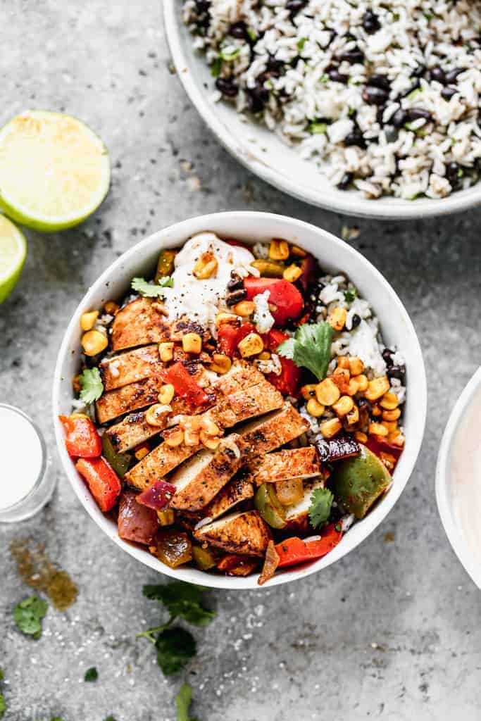 A fajita bowl with rice and black beans topped with grilled vegetables and chicken.
