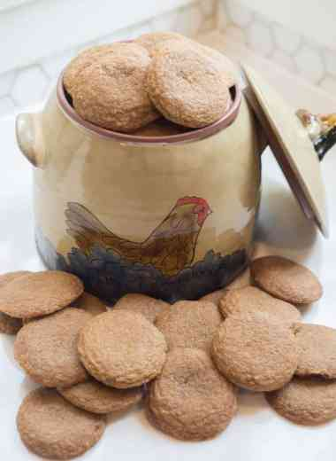 ginger molasses cookies on a white countertop in front of a pottery cookie jar with a hen