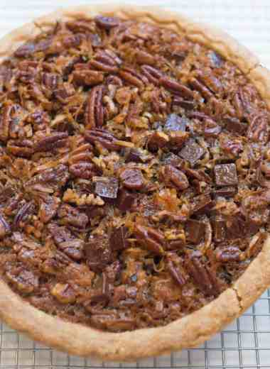 beautiful chocolate coconut pecan pie sitting on a wire cooling rack over a white countertop