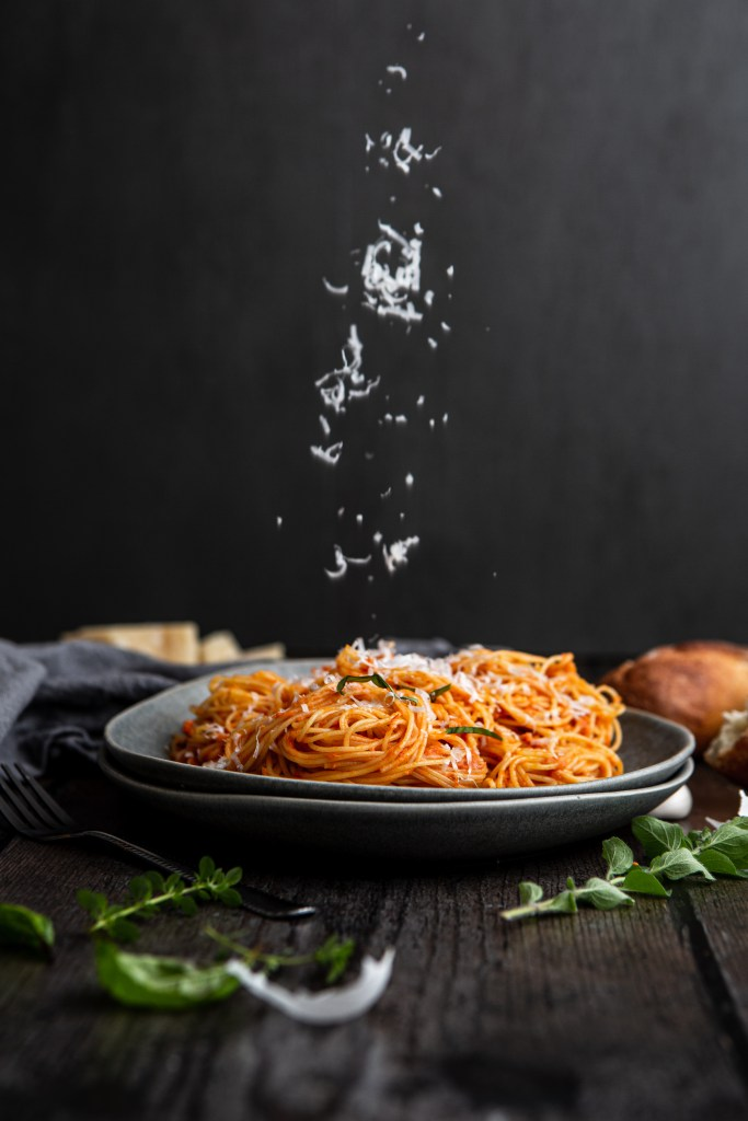 pasta on a plate with parmesan falling on it