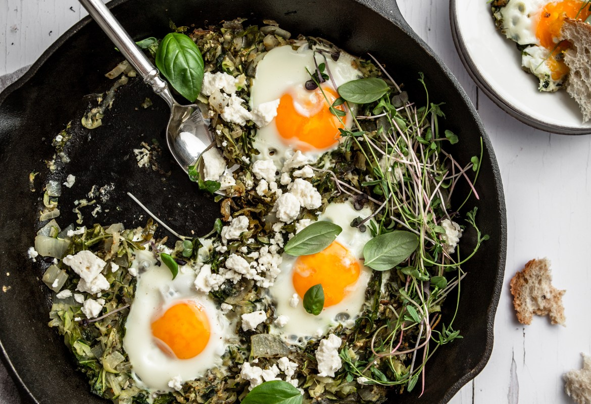 skillet with eggs and vegetables surrounded by torn bread