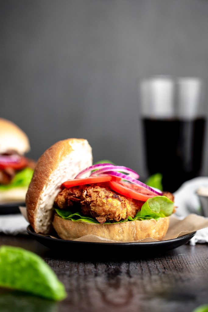 crispy chicken burger with bun top off to the side