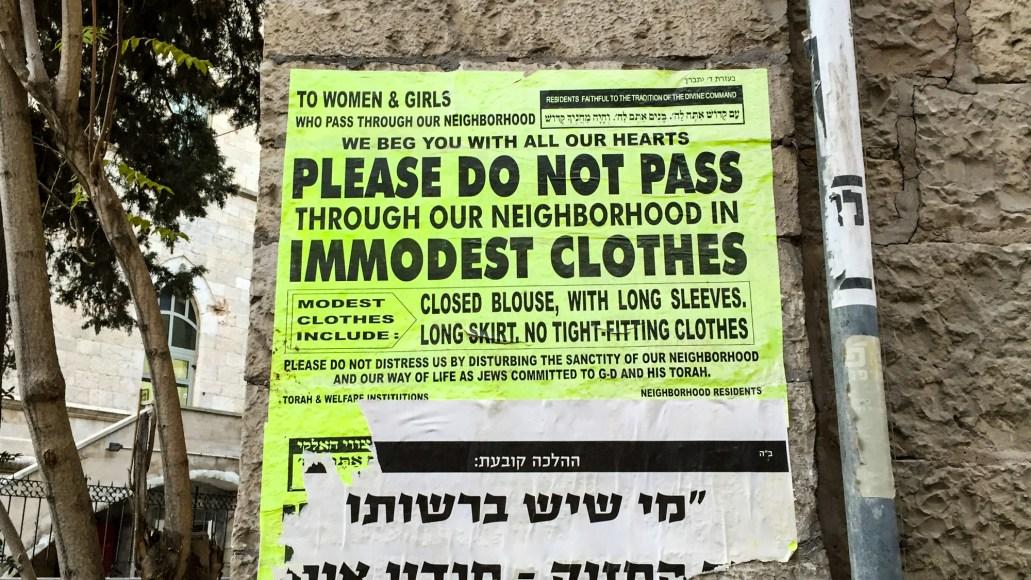 Plakat der opfordrer besøgende kvinder til at gå 'ydmygt' klædt ved indgang til bydelen Mea Shearim