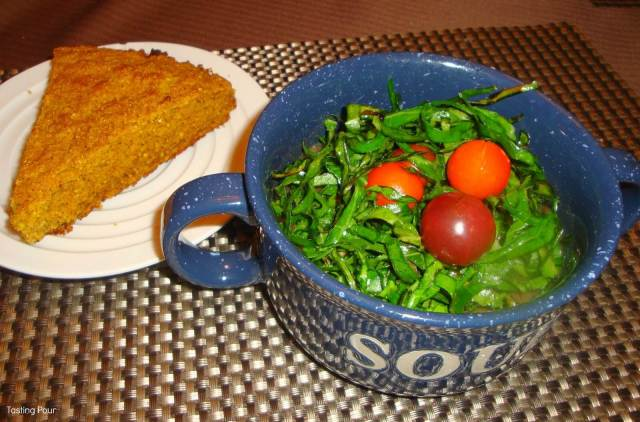 Spaghetti squash soup garnished with shredded collards and cherry tomatoes with pumpkin cornbread