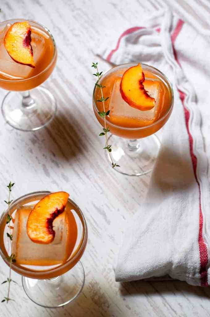 Cocktails with peach and thyme garnishes with a white napkin
