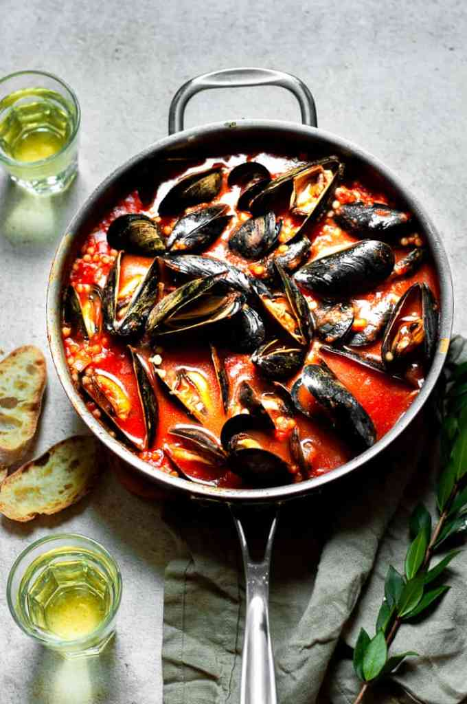 Mussels with Israeli Couscous and Tomato in a pan with bread and wine