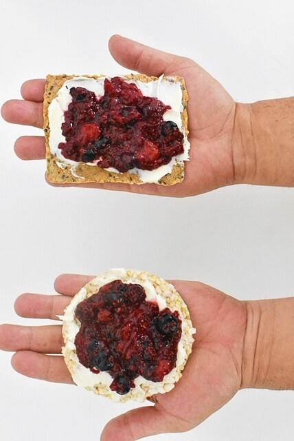 2 hands holding crispbread and brown rice cake topped with mixed berry chia jam and mascarpone cheese