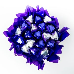 19 purple and silver foil wrapped milk chocolates surrounded by purple cello in a small purple box.