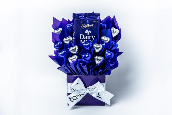 A 180g block of Cadbury Dairy Milk chocolate and 16 purple and silver foil wrapped milk chocolate hearts surrounded by purple cello in a small purple box.