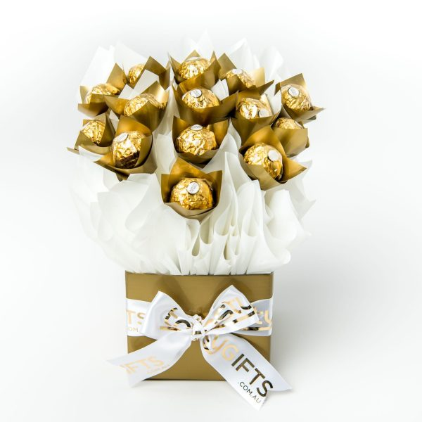 """14 Ferrero Rocher chocolates wrapped in clear and """"leafed"""" with gold cello, all elegantly surrounded in white cello in a small gold box."""