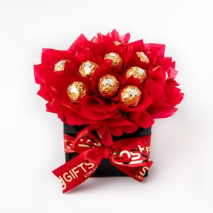 """13 Ferrero Rocher chocolates wrapped in clear and """"leafed"""" in red cello, surrounded by red cello in a small black box."""