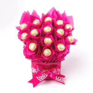 """14 Ferrero Rocher chocolates wrapped in clear and """"leafed"""" with pink cello, all elegantly surrounded in pink cello in a small pink box."""