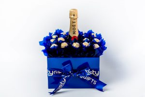 """18 Ferrero Rocher chocolates wrapped in clear and """"leafed"""" in Blue cello around a 750ml bottle of Moët & Chandon Brut Impérial Champagne NV surrounded by blue cello in a large blue box."""