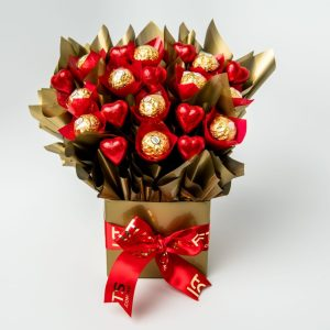 11 Ferrero Rocher chocolates and 9 red foil wrapped milk chocolate hearts surrounded by gold cello in a small gold box.