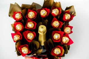 A bottle of Wolf Blass Bilyara sparkling brut accompanied by 15 Ferrero Rocher chocolates, surrounded by gold cello in a medium black box.