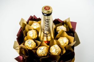"""8 Ferrero Rocher chocolates wrapped in clear and """"leafed"""" in gold cello, all neatly tucked around a bottle of Crown Lager, surrounded by gold and brown cello in a small gold box."""